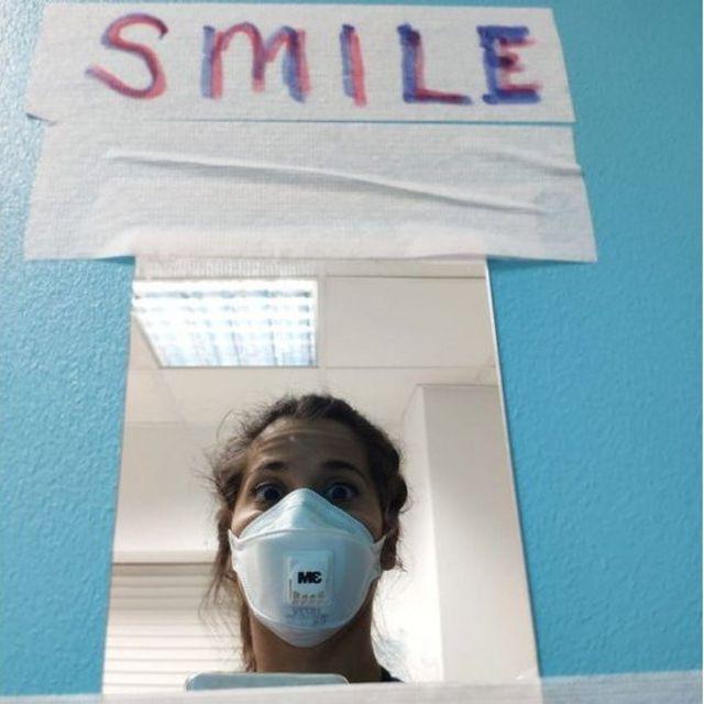 """""""Sonríe. En el área donde nos vestimos y nos ponemos el EPI alguien escribió sobre el espejo este mensaje de ánimo para hacernos sonreir""""."""