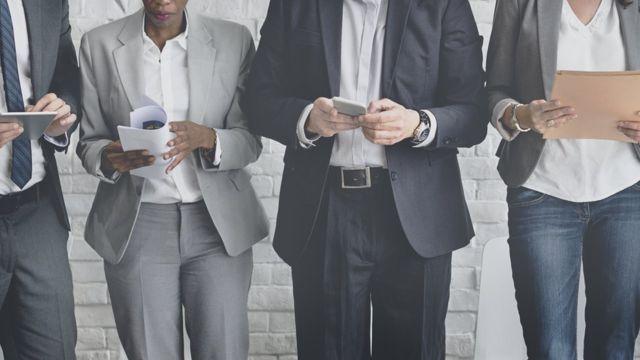 Foto mostra quatro pessoas segurando papéis, celulares e tablets