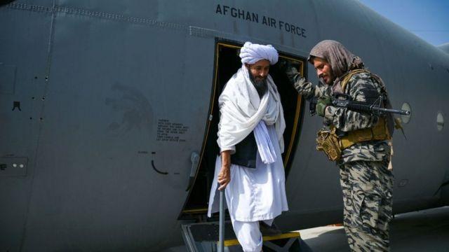 Seorang anggota Taliban turun dari pesawat militer Afghanistan pada 31 Agustus lalu.