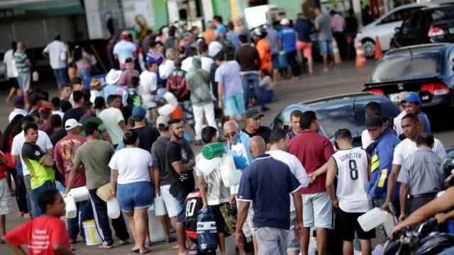 Pessoas e carros fazem fila para comprar combustível em um posto em Luziania (GO), no sétimo dia da greve dos caminhoneiros