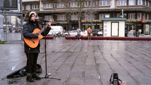 Brüksel'de boş sokaklarda çalan bir müzisyen