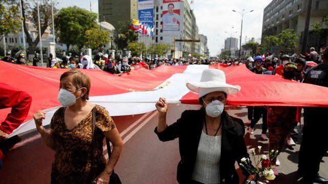 Personas llevan una bandera enorme de Perú por el centro de Lima
