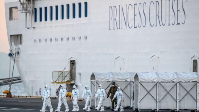 Personal sanitario desciende de un barco en cuarentena.