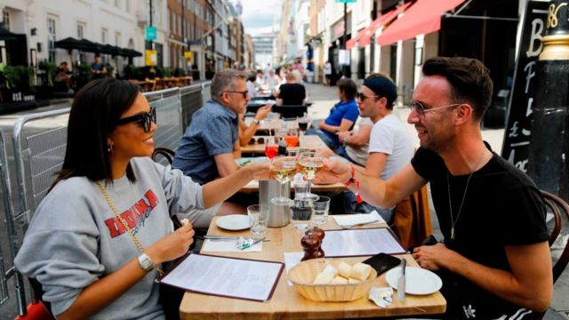 Diners enjoy their drinks as they sit at tables outside a restaurant in London on 3 August, 2020