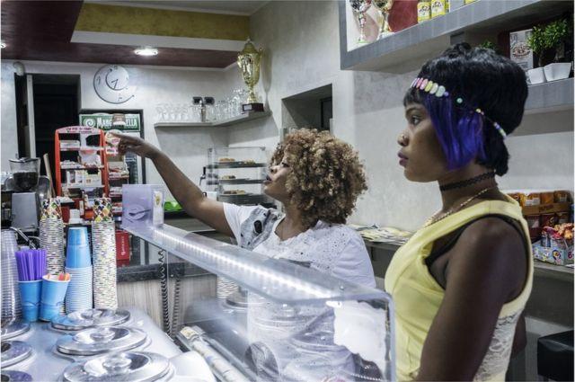 Jennifer 21 ans et son amie viennent du Nigeria. Elles commandent une glace dans l'unique Gelateria de Riace. RIACE (ITALY) 040816