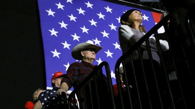 Apoiadores de Trump em fila durante evento, com bandeira dos EUA no plano de fundo