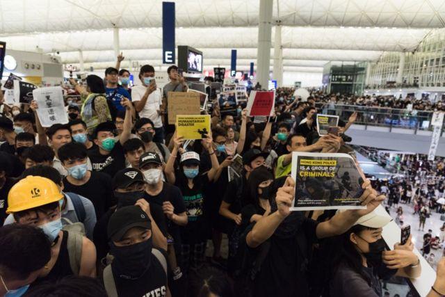 Người biểu tình giơ cao biểu ngữ chống chính phủ tại sân bay quốc tế Hồng Kông trong ngày thứ 5 liên tiếp cho đến tận chiều tối