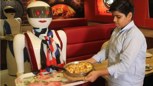 Робот-официант разносит пиццу. Пакистан, июль 2017 года.