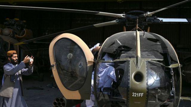 Anggota Taliban mengambil foto helikopter MD-530.