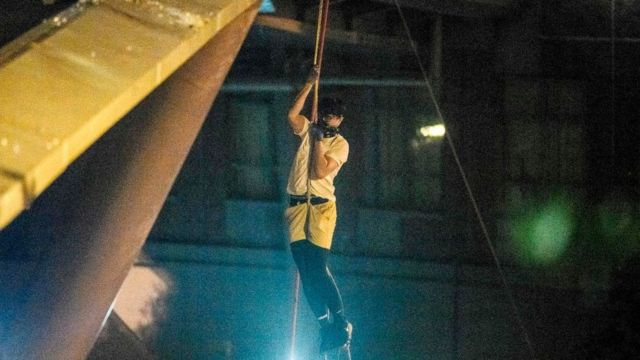 A protester lowers himself down a rope from a bridge to a highway