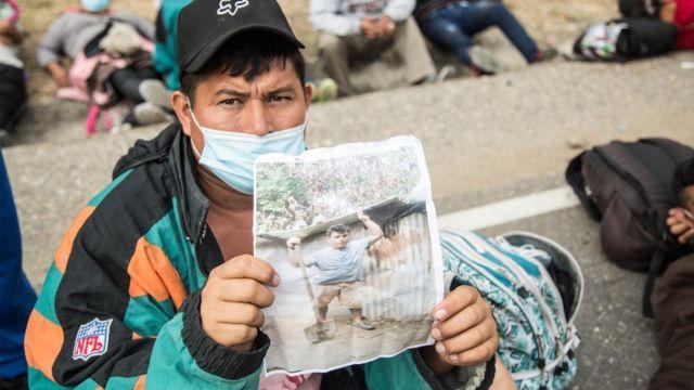 Wilmer, un hondureño de la caravana de migrantes que cruza Guatemala, muestra una foto de su casa destruida por la tormenta Eta, razón por la cual decidió emprender el éxodo de Honduras, mientras descansaba con otros migrantes en Chiquimula, Guatemala.
