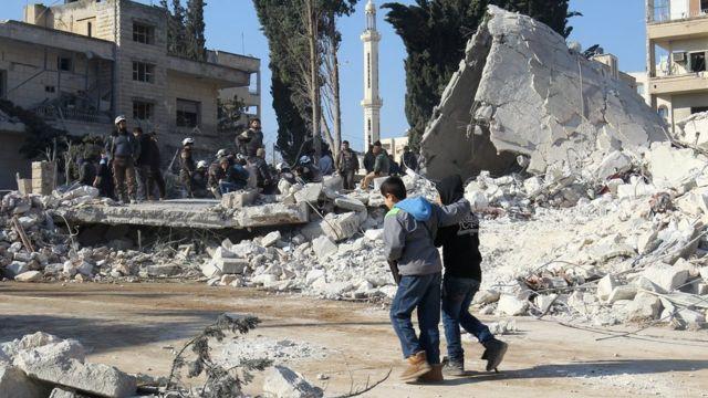 أطفال يسيرون جوار حطام أحد المنازل في سوريا