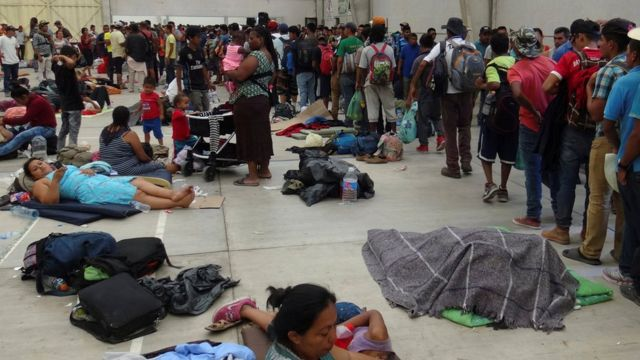 Migrantes descansan en un auditorio