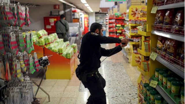 An Israeli policeman searches a supermarket inside the Central Jerusalem Bus Station after police said a woman was stabbed by a Palestinian outside the bus station October 14, 2015.