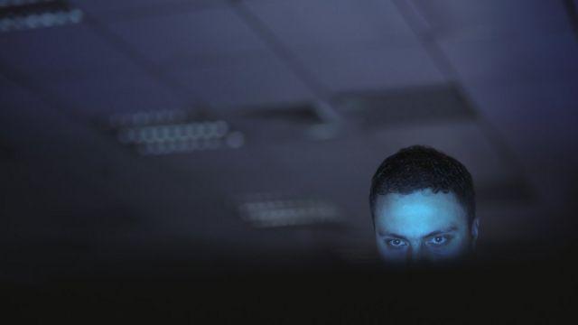 Hombre mirando a la pantalla de una computadora.