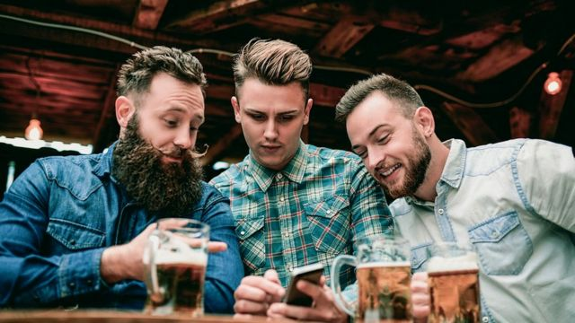 Three men in a bar looking at a mobile phone