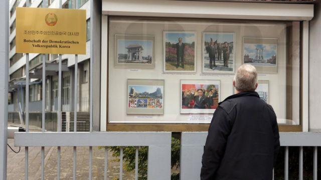 Một du khách xem tranh ảnh cổ động trên bảng tin bên ngoài Đại sứ quán Bắc hàn tại Berlin.