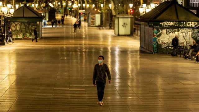 Homem com máscara caminhando pela rua de pedestres à noite