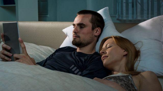 Un jeune couple allongé dans son lit ; il est sur sa tablette numérique, elle dort profondément à côté de lui.