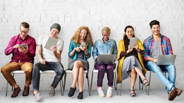 Personas esperando por una entrevista de trabajando, usando sus tabletas, laptops y teléfonos celulares.