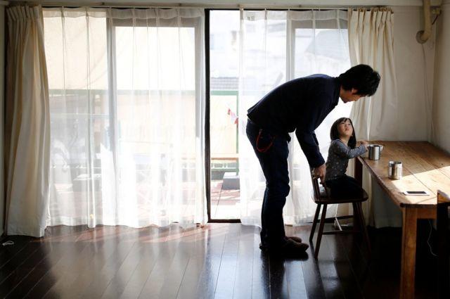 El minimalista Naoki Numahata habla con su hija de dos años y medio, Ei, en la sala de estar, en Tokio