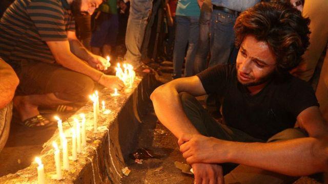Jóvenes lloran frente a unas velas
