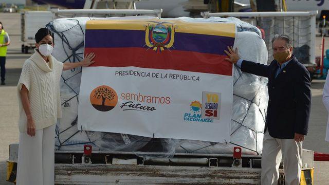 Ministro da Saúde do Equador, Juan Carlos Zevallos, e a vice-presidente do país, María Alejandra Muñoz, posam junto ao primeiro lote da vacina que chegou ao país em 21 de janeiro