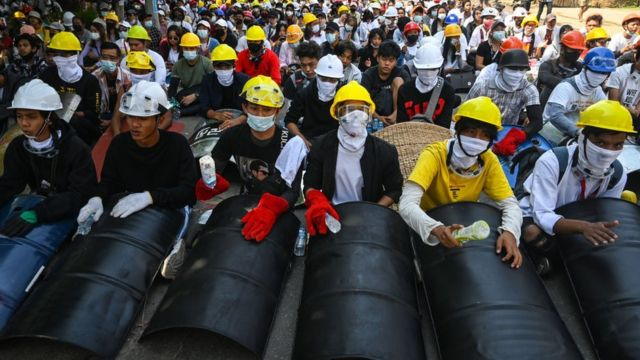 Protesters wear protective equipment and hold homemade shields as they prepare to face off against security forces during a demonstration against the military coup in Yangon on March 5, 2021.