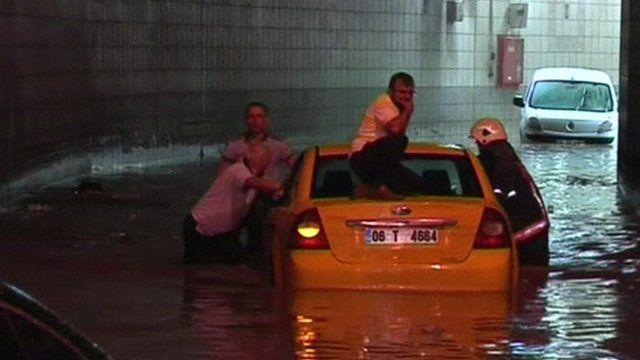 A man sits on his car roof as emergency services push it