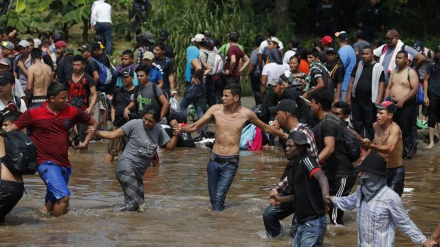 Mostly Honduran migrants cross a river that separates Guatemala and Mexico on 29 October 2018