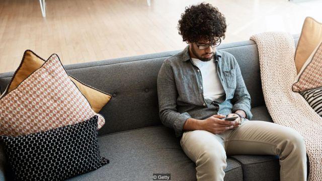 Imagem mostra homem sentdo no sofá usando o smartphone