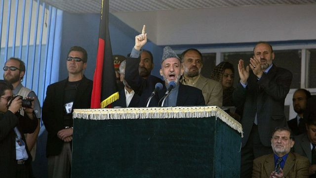 Hamid Karzai dando un discurso rodeado de personas.