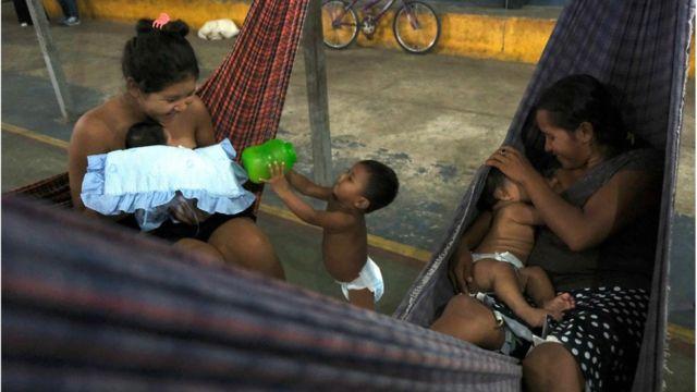 Duas mulheres warao, sentadas em redes, com bebês no colo e uma criança de frauda entre as redes