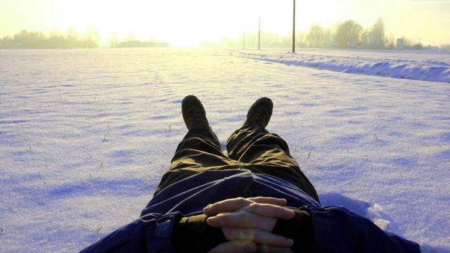 Un hombre descansa acostado en la nieve