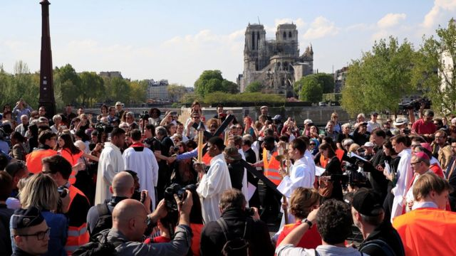 People attend a procession close to Notre-Dame