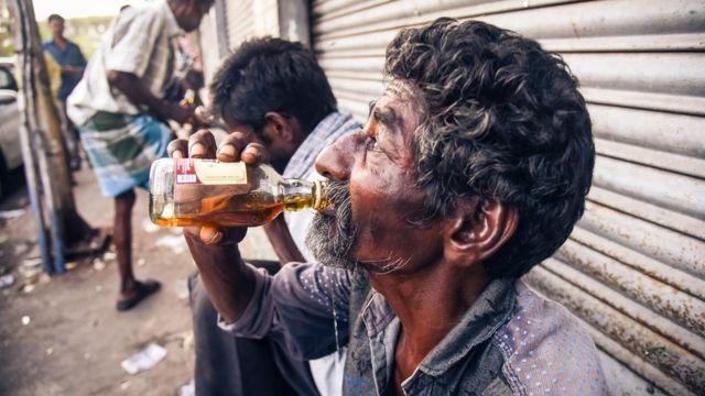 Un hombre bebe alcohol fuera de una licoreria en India.
