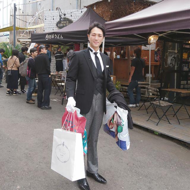 Yuichi Ishii vêtu d'un costume noir, d'un gilet noir et d'une cravate noire avec des gants blancs