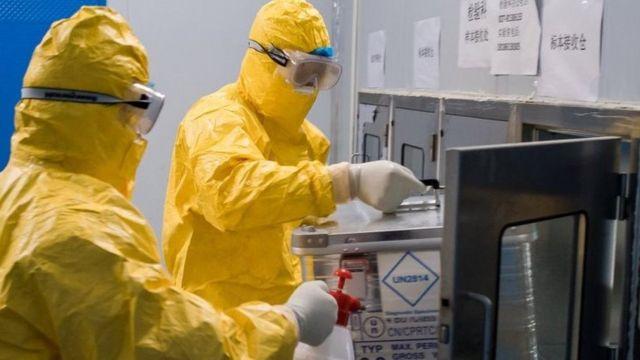 「病毒樣本快遞員」劉森波與同事梅乙奇將病毒樣本從箱倉取出。他們每日要跑兩趟到武漢雷神山醫院收取樣本。