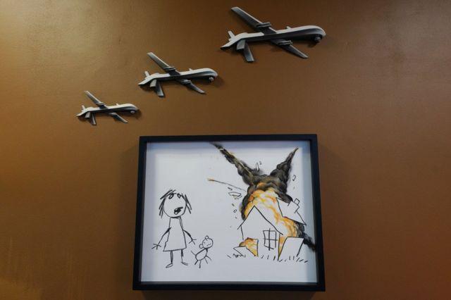 Sanatçı Banksy, Uluslararası Silah Fuarı'nı protesto etmek için kurulan Uluslararası Silah Fuarı Sanat Sergisi'nde bu eserini sergilemişti