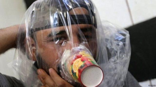 ઇદલિબમાં રાસાયણિક હુમલા સામે રક્ષણની તૈયારી કરતી માસ્કધારી વ્યક્તિ