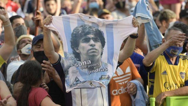 Seguidores de Diego Maradona con una camiseta con el rostro del jugador.
