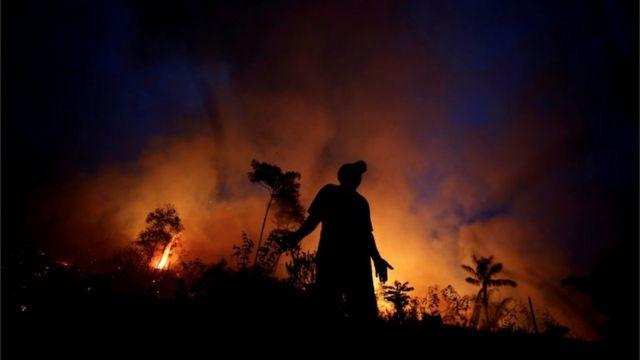 Homem diante de incêndio na Amazônia