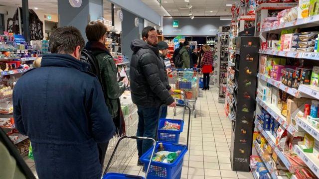 People queue to buy food in Milan as quarantine measures are announced