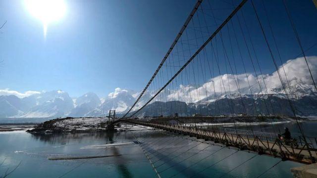 Un puente sobre el río Indo con vistas de los glaciares al fondo