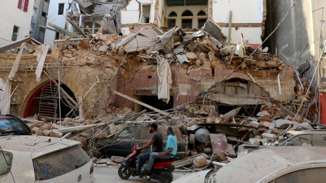 Men ride a motorcycle past a damaged building