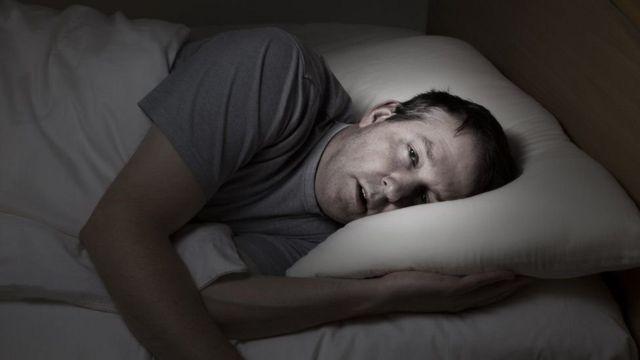 Homem na cama tentando dormir