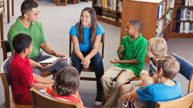 Ronda de alumnos con maestro hablando.