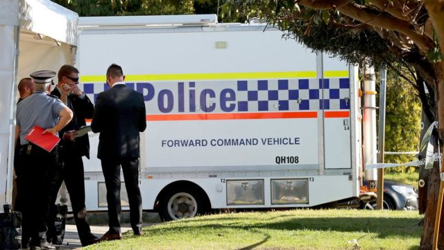 Police are seen at a property in Bedford, Perth after a group of people were found dead