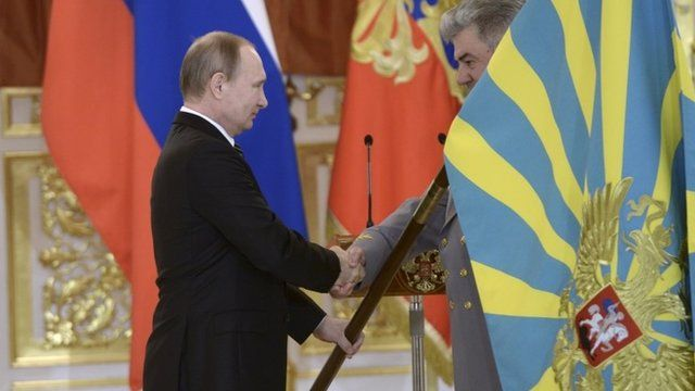 Russian President Putin hands over a flag to a returning serviceman