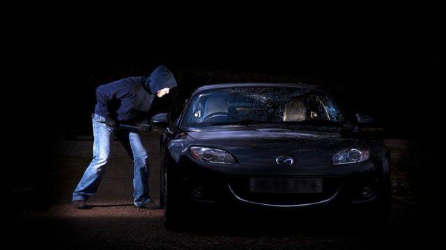 Homem tentando arrombar um carro